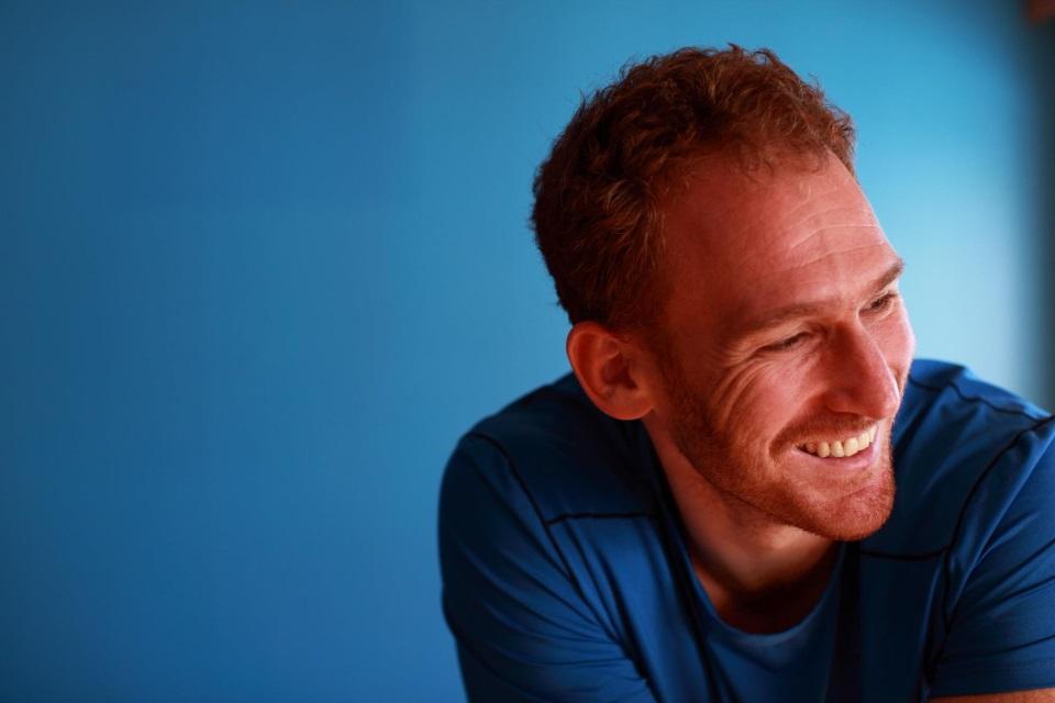 Jordan Bloom vor blauem Hintergrund Portrait - YogaCircle Berlin